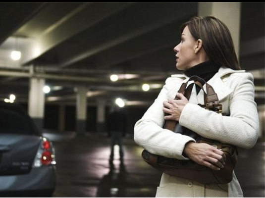 Safety tips from MVP Protective Services, a Washington, DC based Security company. This photo shows a woman walking through a parking lot with a suspect following.