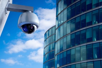A globe CCTV camera with a building in the background