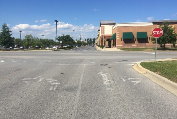 Shopping center with faded crosswalk and traffic signs