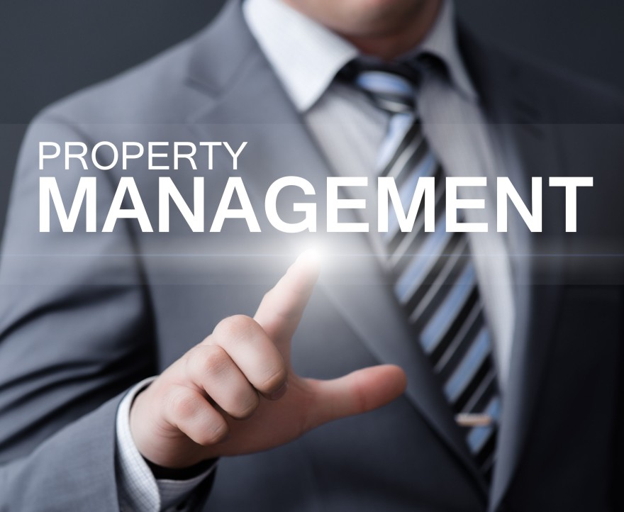 Man pointing to a sign that says property management.
